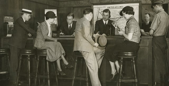 Men assisting people at a ticket office, circa 1920s-1930s. (The Steve A. Stimpson Photograph Album/The Museum of Flight)