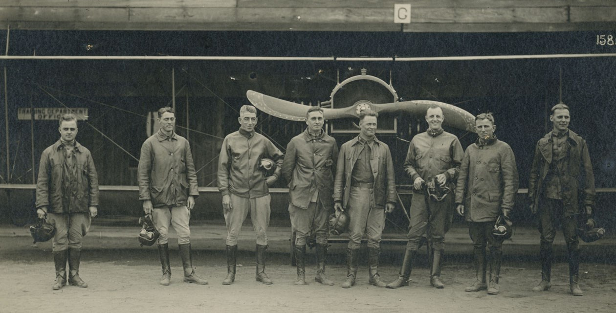 Eight pilots of the Junior Military Aviator Class, Signal Corps Air Service, standing in front of a Curtiss JN-4 Jenny biplane, 1917.