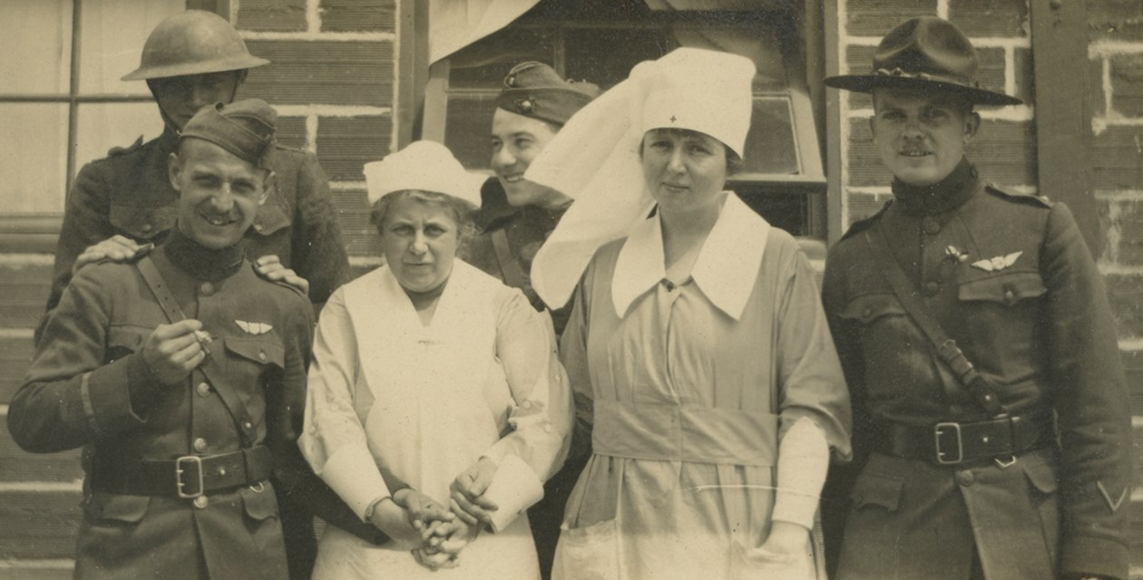Four soldiers and two nurses posing together outside a brick building, circa 1917-1919.