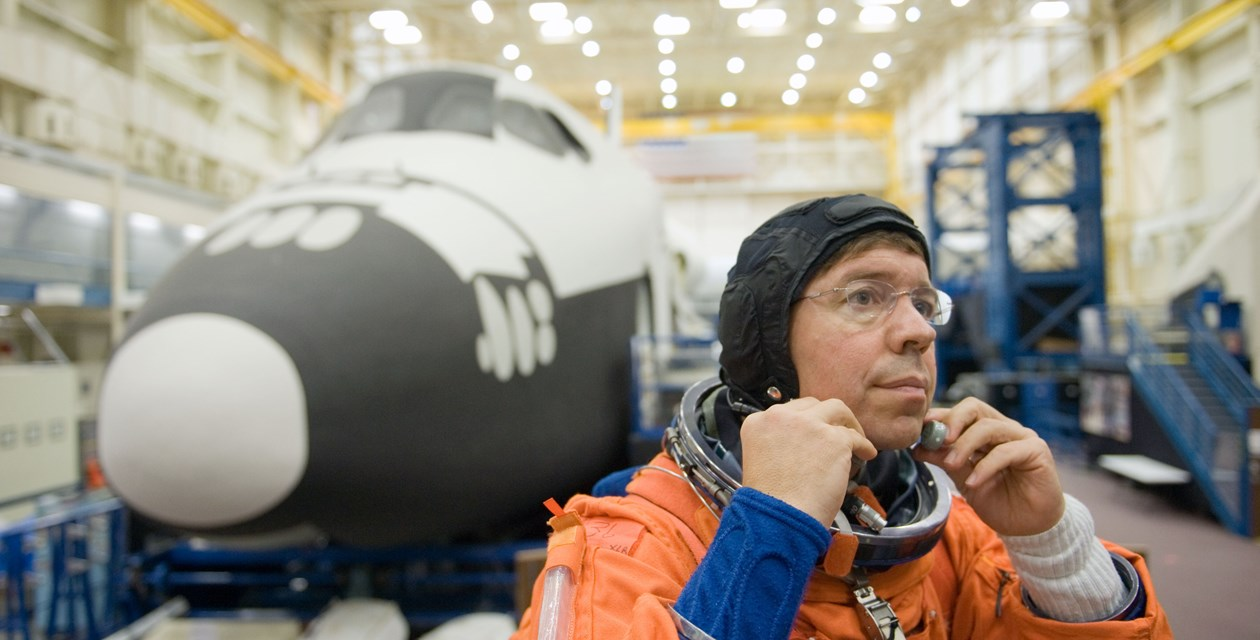 Barratt and FFT - NASA astronaut Michael Barratt, STS-133 mission specialist, dons a training version of his shuttle launch and entry suit in preparation for a training session in the Space Vehicle Mock-up Facility at NASA's Johnson Space Center. The space shuttle Full Fuselage Trainer in the background is now on exhibit at The Museum of Flight, Seattle. Photo credit: NASA. (24 Sept. 2010)